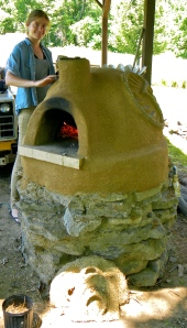 Anna painting on the cob oven while being fired for a pizza party