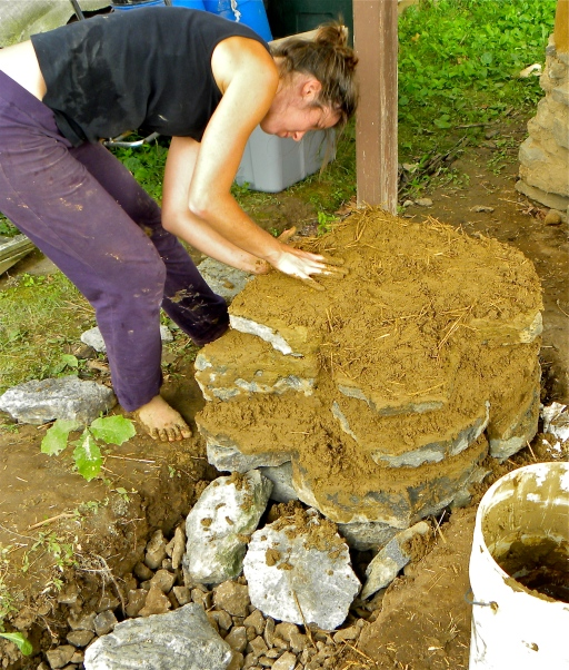 Eva capping the rocket stove foundation with cob